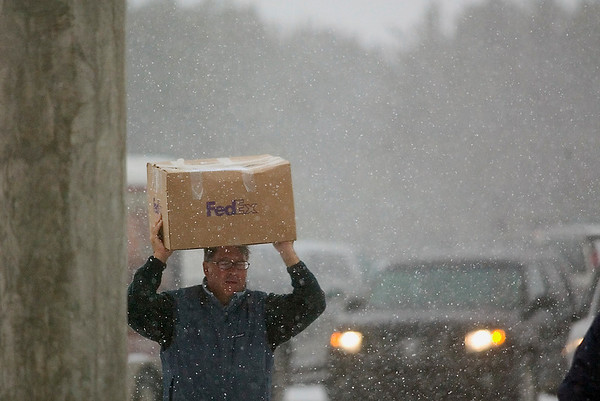 Record-Eagle/Jan-Michael Stump<br /> Mike Simpson of KBar North America carries a box through Friday's snow to set up for this weekend's Home Expo, sponsored by the Home Builders Association of the Grand Traverse Area, Friday at Traverse City East Middle School.
