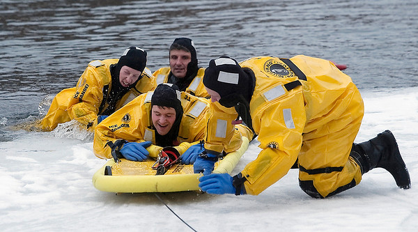 Record-Eagle/Douglas Tesner<br /> Traverse City Fire Department Capt. Marco Marcantoni and firefighters Steve Ball, Keith Fritz and Jerry Wojtanowski practice ice rescues on the Boardman River near the Cass Street dam during their annual ice water rescue training.