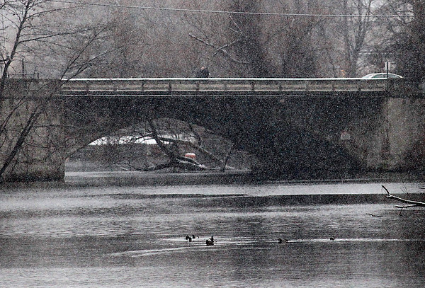 Record-Eagle/Jan-Michael Stump<br /> Pedestrians make their way over the Boardman River on Union Street as the storm begins.
