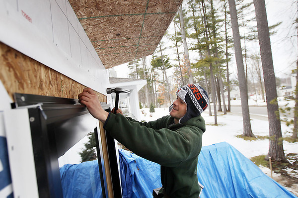 Record-Eagle/Keith King<br /> Rex Demski, of Flint, installs a sliding door during construction on a new home at the Fairway Hills residential development in Traverse City.