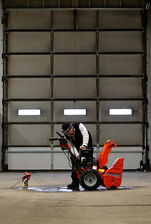 """Record-Eagle/Jan-Michael Stump<br /> Traverse City Department of Parks and Recreation employee Cindy Anderson cleans a snowblower at the Gerald """"Buck Williams Department of Public Services building."""
