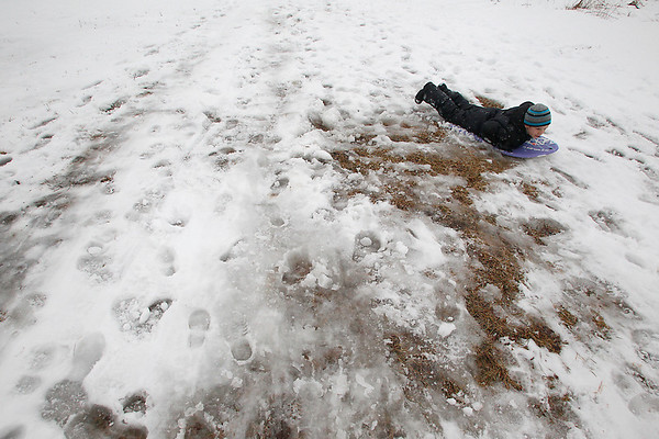Record-Eagle/Jan-Michael Stump<br /> Desmond Turner, 7, avoids a patch of exposed grass while sledding at his home in Solon Township last month.