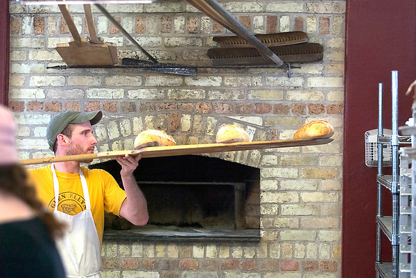 Record-Eagle/Jan-Michael Stump<br /> Kevin McGrath removes loaves of bread from the oven at Pleasanton Brick Oven Bakery. The bakery is one of the competitors in the upcoming Edible Art Show at the Village at Grand Traverse Commons.