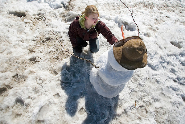 Record-Eagle/Jan-Michael Stump<br /> Jenna Montcastle of Traverse City puts the finishing touches on a snowman she built with Jake Rahe (not pictured) along Grandview Parkway at the Open Space on Tuesday afternoon.