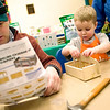Record-Eagle/Jan-Michael Stump<br /> Ben Minor of Interlochen helps his son Charlie, 2, make a firehouse bank at the Home Depot Kids Expo while visiting the Home Expo Saturday with his wife Genevieve and their other son Matthew, 7 months. The family was at the show to look for ideas to make their home more saleable.