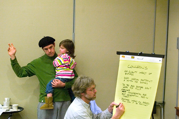 Record-Eagle/Jan-Michael Stump<br /> Todd M. Brown holds his daughter Camille, 3, while waiting to comment. Facilitator Jonanthan Pool writes down the group's ideas during a forum hosted by Traverse City Light and Power Saturday at the Hagerty Center.