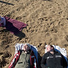 """Record-Eagle/Jan-Michael Stump<br /> Eva Zindler, 4, plays in the sand while her mother, Laura Schewe, and Laura Bowen relax on Clinch Beach on Friday afternoon. """"You can't not soak up the sun this time of year; we're all vitamin D deficient,"""" said Bowen."""