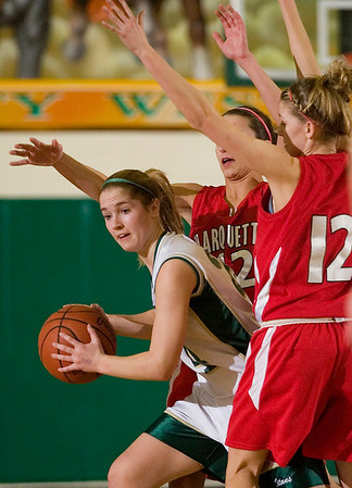 Record-Eagle/Jan-Michael Stump<br /> Marquette's Alicia Romano (42) and Jade Ledy (12) put pressure on Traverse City West's Mallory Litwiller (24) in the first quarter of Monday's game.