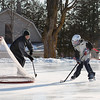 Record-Eagle/Keith King<br /> Jerry Linenger, of Suttons Bay, and his 12-year-old son, Henry Linenger, play hockey Saturday at the park near the intersection of Broadway and Lincoln streets in Suttons Bay. Henry, who plays on Dave Harvey's Pee Wee AA travel hockey team coached by former Detroit Red Wing, Dallas Drake, was practicing for an upcoming tournament.