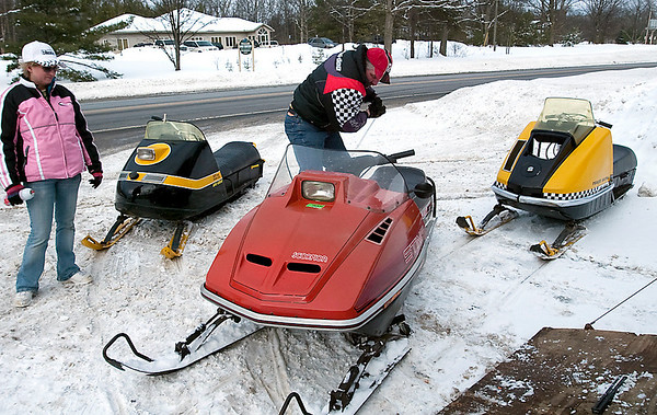 Record-Eagle/Douglas Tesner<br /> Doug Prause and his wife display his vintage snowmobiles in front of Giovanni's Roadhouse in Interlochen. Prause will display his snowmobiles at the Ninth annual Antique Snowmobile Show in Karlin Saturday.