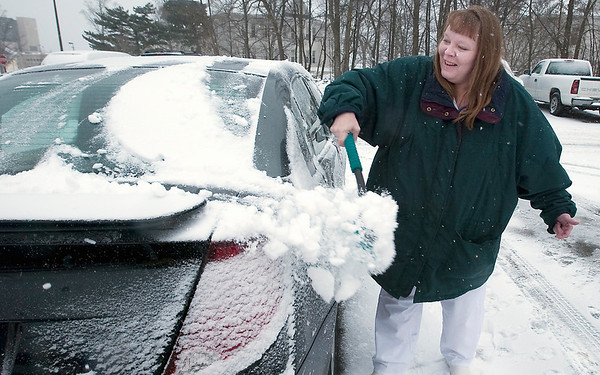 Record-Eagle/Douglas Tesner<br /> Deneen Reynolds, a nursing student at NMC, cleans the snow off her car Tuesday as she leaves clinical training at Munson Medical Center and heads to her full-time job at an adult foster care home.