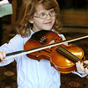 Record-Eagle/Lisa Perkins<br /> Ally Jo McKenna, 4, tried out the violin during pre-concert activities, including a musical instrument petting zoo, before Saturday's Traverse Symphony Orchestra free children's concert, featuring S.O.U.L., Singers of United Lands.