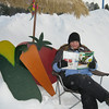 Michelle Wallace, one of the organizers of VEGGO, a group starting a community garden in Kalkaska, reads a seed catalog in a snowbank as she dreams of spring.