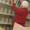 Record-Eagle/Lisa Perkins<br /> Dorothy Westrate helps fill shelves prior to the opening of the Kingsley Public Library's new location on Tuesday.
