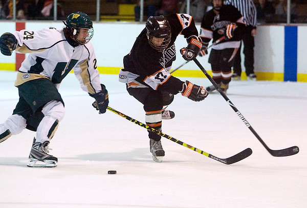 Record-Eagle/Jan-Michael Stump<br /> Brother Rice forward Stephen Hibbard (17) and Traverse City West forward Nick VandeKieft race for the puck.