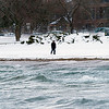Record-Eagle/Douglas Tesner<br /> A man braves the blowing wind and cold weather as he walks Clinch Park Beach on Grand Traverse Bay Monday.