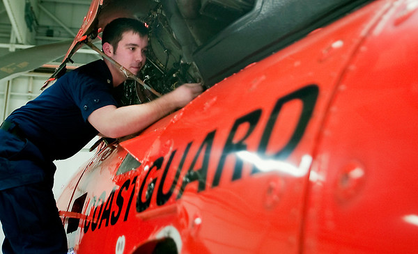 "Record-Eagle/Douglas Tesner<br /> U.S. Coast Guard aviation electronics technician William Morrow inspects the engine area on one of the HH-65C ""Dolphin"" helicopters at the air station in Traverse City. The city is up for approval as the 10th Coast Guard city in the nation and the second in Michigan."