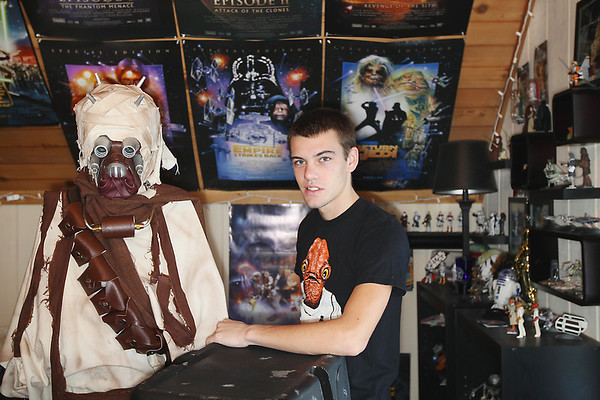 "Record-Eagle/Keith King<br /> Zach Titus, of Traverse City, stands in his room near a ""Star Wars"" character he constructed himself as well as other ""Star Wars""-themed props and collectibles. Beginning next month, Titus will be an intern at Walt Disney World Resort through the Disney College Program and will be working in the area of costume and prop production. Titus -- a member of the 501st Legion, a ""Star Wars"" costuming organization -- will also join the Florida Garrison, which volunteers at Disney's ""Star Wars"" attraction."