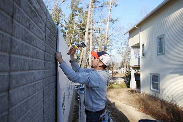 Record-Eagle/Keith King<br /> Mark Coykendall, with Portz Builders, applies house wrap as he works in the Fairway Hills subdivision.