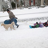 Record-Eagle/Jan-Michael Stump<br /> John Sonnemann pulls sleds with his grandchildren, from left, Blake Weaver, 2; Emma Dykstra, 3; and Luke Weaver, 4, as they walk with his labradoodle, Toby, home from a trip to F&M Park on Wednesday afternoon.