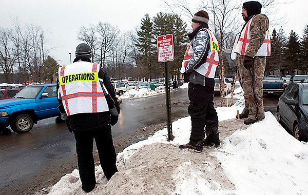 Record-Eagle/Douglas Tesner<br /> Left to right, Chris Meredith, Trever Schaub and Travis Cripe, temporary employees from Michigan Manpower, look over one of the parking lots at Northwestern Michigan College to see if there are any spaces open.