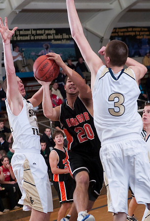 Record-Eagle/Douglas Tesner<br /> John Mathews of Harbor Springs tries to split St. Francis defenders Ian Sheldon, left, and Sean Sheldon during Tuesday's Lake Michigan Conference game.