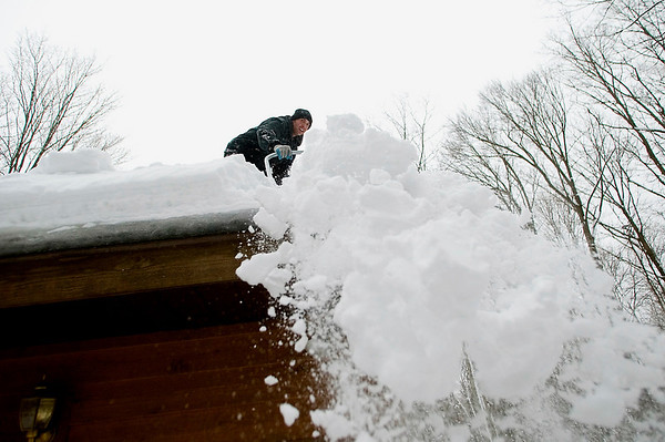 Record-Eagle/Jan-Michael Stump<br /> Josh McCormick shovels the roof of a home in Long Lake Township on Thursday afternoon.