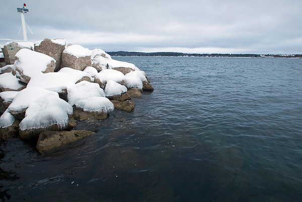 Record-Eagle/Jan-Michael Stump<br /> Snow and ice cover the docks and rocks at Traverse City's Clinch Park Marina on Grand Traverse Bay's West Arm Wednesday afternoon. Water levels are higher here and in the rest of the Great Lakes after being below normal two years ago.