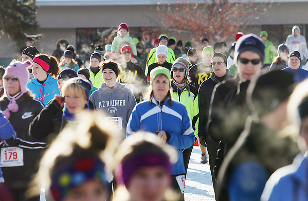 Record-Eagle/Keith King<br /> Participants in the annual Traverse City Track Club Frozen Foot 5 Mile race make their way toward the starting line Saturday on Eastern Avenue.