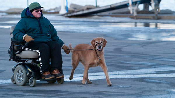 Record-Eagle/Douglas Tesner<br /> <br /> Jeanne Esch and her golden retriever Tucker, take their evening walk through Clinch Marina Park.  Esch suffers from a neuromuscular disease and her friend Tucker is a service dog.  Tucker was not pulling her but running by her side.