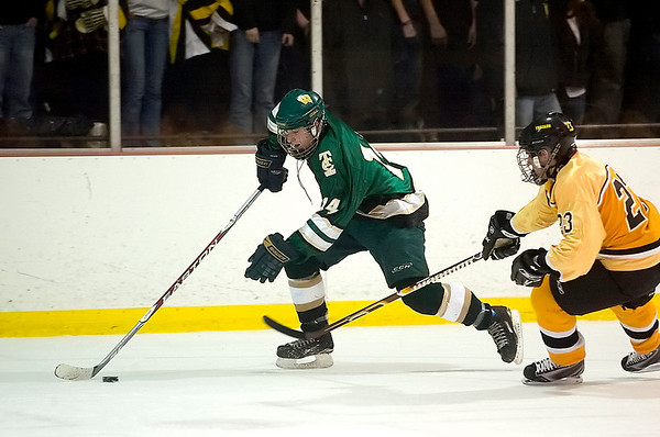 Record-Eagle/Jan-Michael Stump<br /> Traverse City West defenseman Frank Gilbert (14) skates past Traverse City Central defenseman Christian Machelski (23) in the first period Wednesday at Howe Arena.