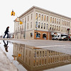 Record-Eagle/Keith King<br /> A puddle reflects a pedestrian crossing Union Street at Front Street on Wednesday in downtown Traverse City.