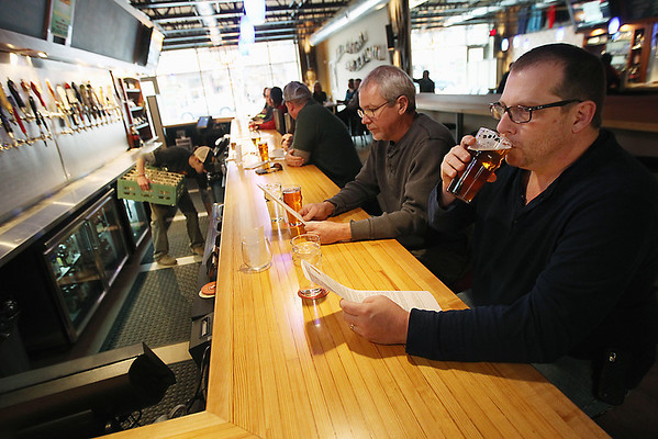 Record-Eagle/Keith King<br /> Bellaire residents Dave Runyan, right, sips his beer as Gary Streitwieser looks over a menu at 7 Monks Taproom in downtown Traverse City.