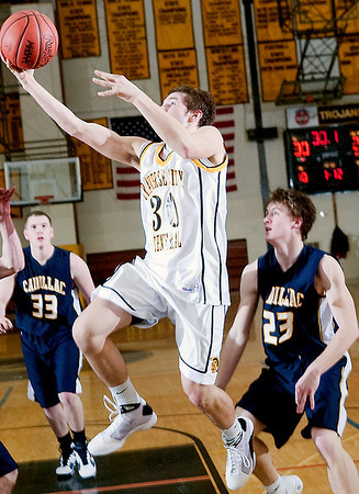 Record-Eagle/Douglas Tesner<br /> TC Central's Dylan Roe (30) goes to the hoop as Cadillac's Mike Weeks (23) and Connor Parcell (33) watch.