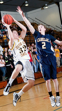 Record-Eagle/Douglas Tesner<br /> TC Central's Mack Sovereign (32) shoots around Cadillac's Matt Dunbar (2).