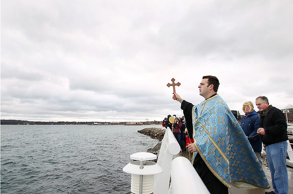 Record-Eagle/Keith King<br /> Father Ciprian Streza, of the Archangel Gabriel Greek Orthodox Church in Traverse City, prepares to toss a cross into West Grand Traverse Bay on Saturday during the Great Blessing of the Waters on the Clinch Park Marina pier.