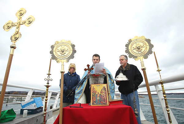 Record-Eagle/Keith King<br /> Lou Condos, left, of Traverse City, and Steve Bemis, right, look on as Father Ciprian Streza of the Archangel Gabriel Greek Orthodox Church, in Traverse City, conducts the Great Blessing of the Waters at Clinch Park Marina on Saturday.