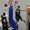 Record-Eagle/Jan-Michael Stump<br /> Traverse City St. Francis forward Sean Sheldon (31) dunks over Grayling guard Scott Parkinson (2) in the second quarter of Tuesday's game.