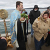 Record-Eagle/Keith King<br /> Donna Fickling, front, of South Boardman, walks away after being blessed with holy water on the Clinch Park Marina pier by Father Streza blesses her with holy water.