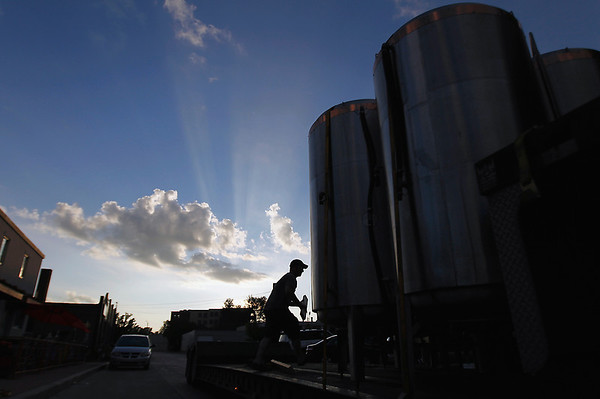 """Record-Eagle/Jan-Michael Stump<br /> Right Brain Brewery owner Russell Springsteen and helpers unload bright tanks used in the brewing process from truck late afternoon Monday in Traverse City' Warehouse District. Springtseen bought the equipment at an auction downtstate because the deal was too good to pass up, he said. """"Now I have options, which is good."""""""