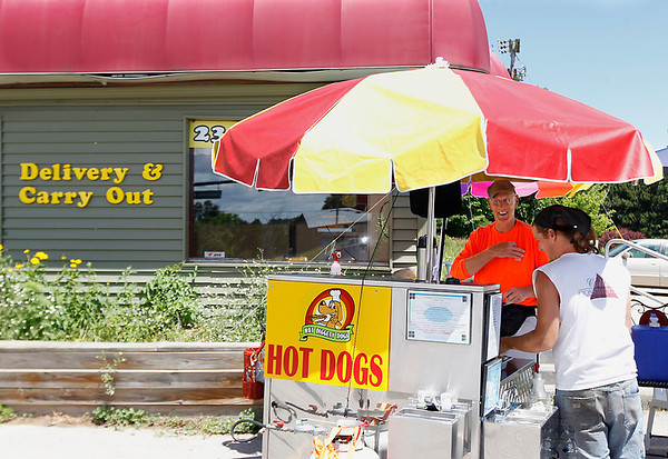 Record-Eagle/Jan-Michael Stump<br /> Norbert Tutlis makes a hot dog for Darryl Hallman on Wednesday afternoon at his hot dog stand at the intersection of Zimmerman and Silver Lake Roads.