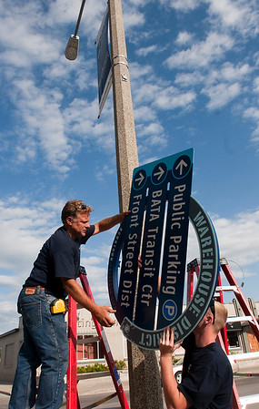 Record-Eagle/Douglas Tesner<br /> Thom Becker, left, and Bud King, of Valley City Signs, install signs for the new wayfinding system in downtown Traverse City.