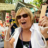 Record-Eagle/Jan-Michael Stump<br /> Cindy Klepper cheers for the Bullock Creek Marching Band from the front of her Union Street home during the Cherry Royale Parade. Cindy and husband Ray began cheering for marching bands about 30 years ago from their home, which sits near the end of the parade route.