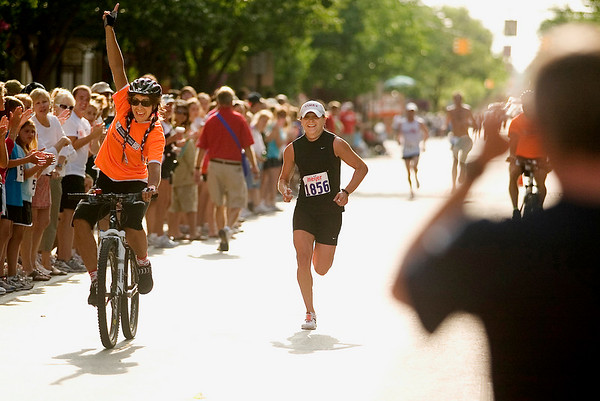 Record-Eagle/Jan-Michael Stump<br /> With an escort, 15k women's winner and Kalkaska native Sara Vergote nears the finish line in Saturday's Meijer Festival of Races.