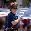 Record-Eagle/Jan-Michael Stump<br /> Members of the Traverse City Fire Department, Grand Traverse Metro Fire Department, Grand Traverse Rural Fire Department, and the United States Coast Guard carry an American flag during Saturday's Cherry Royale Parade.