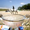 Record-Eagle/Keith King<br /> The trophy for the $10,000 Open Jumper Welcome Prix is displayed as a horse and rider exit after completing the course during the 2010 Horse Shows by the Bay at the Flintfields Horse Park in Williamsburg.