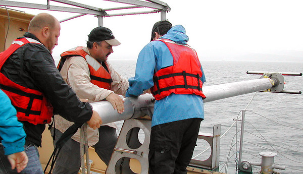Record-Eagle/Sheri McWhirter<br /> Jack Rowell, Michigan Sea Grant's Mark Breederland and volunteer Scott Swan work together to pull the sonar equipment back onboard the Northwestern after a couple of hours of mapping the bottom of the bay on Wednesday.