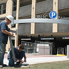 Record-Eagle/Jan-Michael Stump<br /> David Dibenedetto, left, and Kevin Adams install bollard lights along the sidewalk outside the Old Town Parking Deck, which is set to open today.