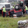 Record-Eagle/Douglas Tesner<br /> Firefighters and paramedics work to remove the driver of a Jeep Wrangler that was pinned under a truck after a collision on M-22 and East Revold Road. Details on the driver's condition were not known at press time.