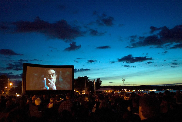 """Record-Eagle photo/Jan-Michael Stump<br /> """"Men in Black"""" was shown on the big screen at the Open Space during the opening night of the fifth annual Traverse City Film Festival. The screen's new spot on the Open Space allowed for more people to have a clear view of the screen, while a fence kept light from passing traffic on Grandview Parkway to a minimum."""